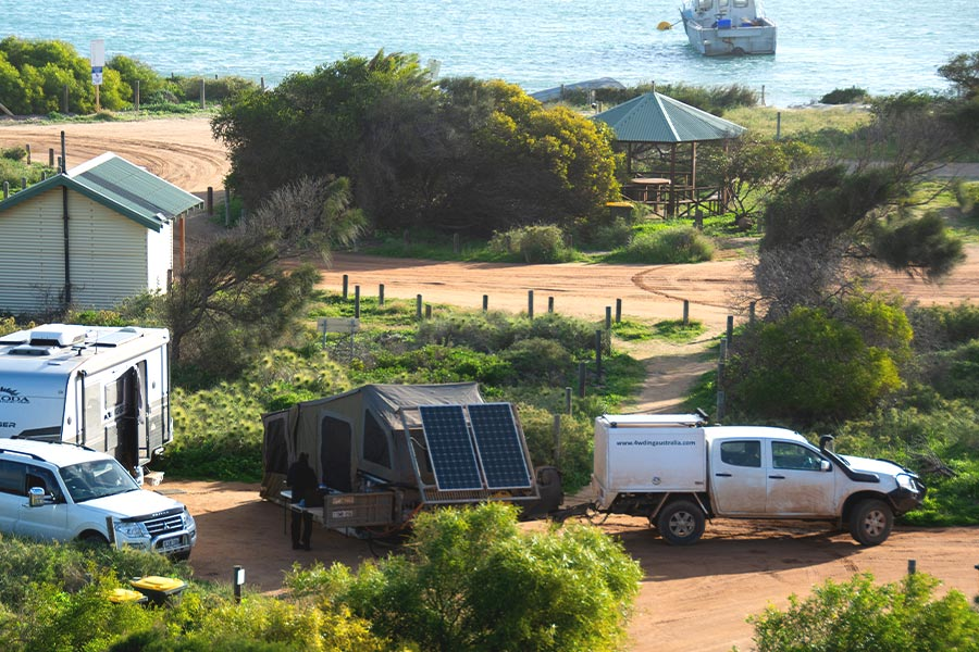 A camper trailer and caravan with 4WD vehicles set up at a coastal campsite. There are trees and shrubs, a toilet block and picnic area with the sea in the background.