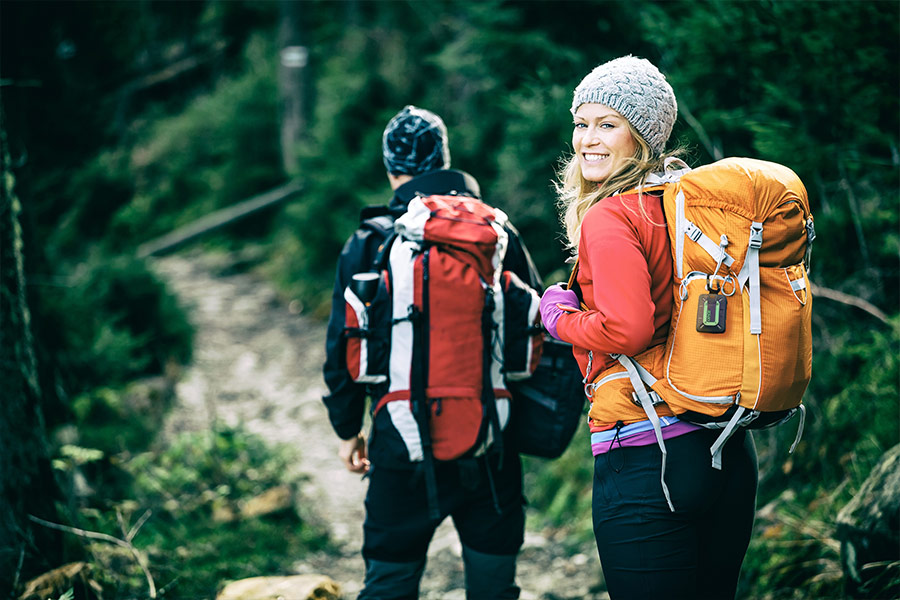 Two hikers walk along a trail with green foliage around. They are both carrying rucksacks and the female hiker has a ZOLEO Satellite Messenger attached to her orange rucksack.