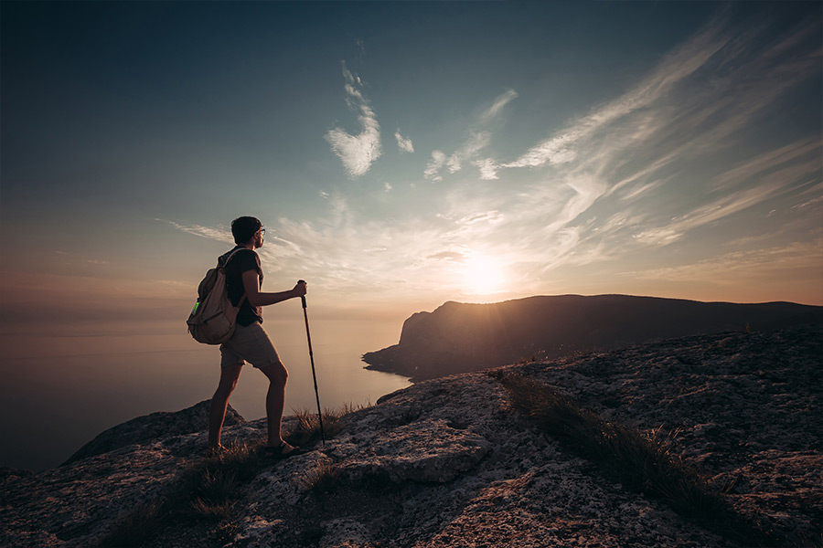 A lone male hiker holds a trekking pole as he reaches the summit of a coastal mountain at sunrise. He's wearing a backback with a ZOLEO messenger device attached to the top.