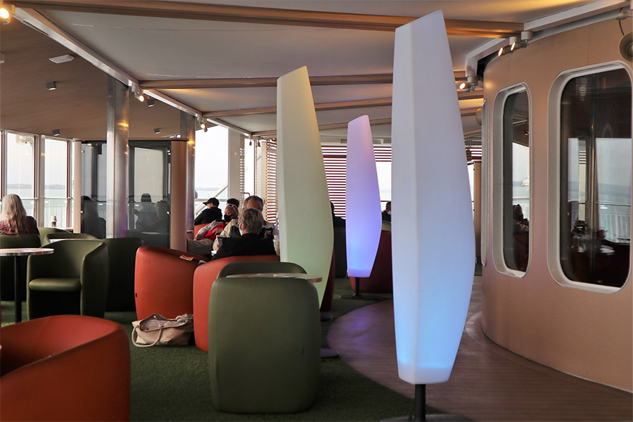 A seating area onboard the Spirit of Tasmania with green and red pod chairs, and round tables. There are sculpted light stands marking out a walkway.
