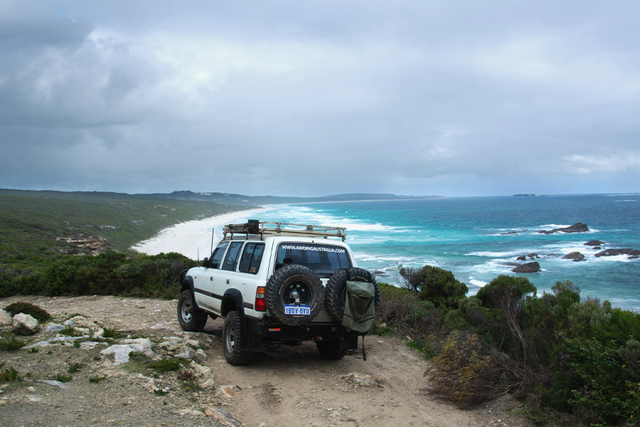 A white 4WD Landcruiser is parked atop a cliff looking out over the beach and ocean below. There are grey rainclouds overhead.