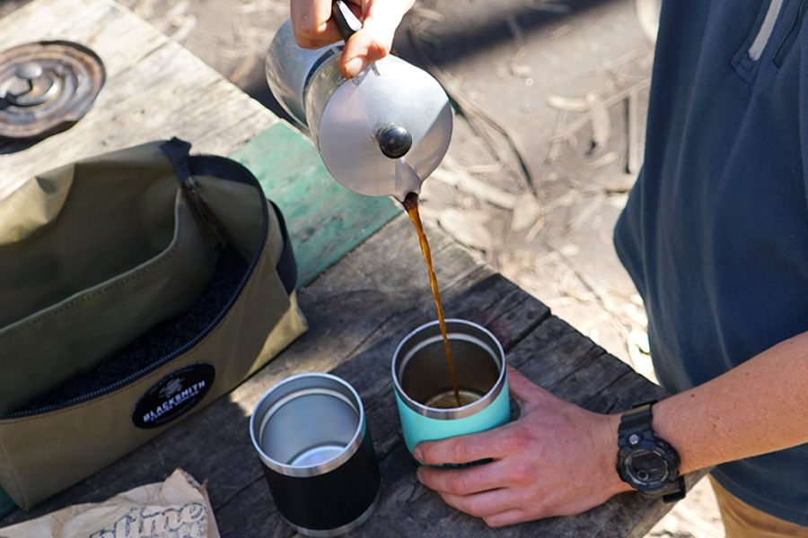 Close-up of a rustic outdoor table top with a man's hands pouring freshly brewed coffee from a stove top percolator into two insulated cups. There's a green canvas Blacksmith Coffee Kit Bag on the table next to the cups.