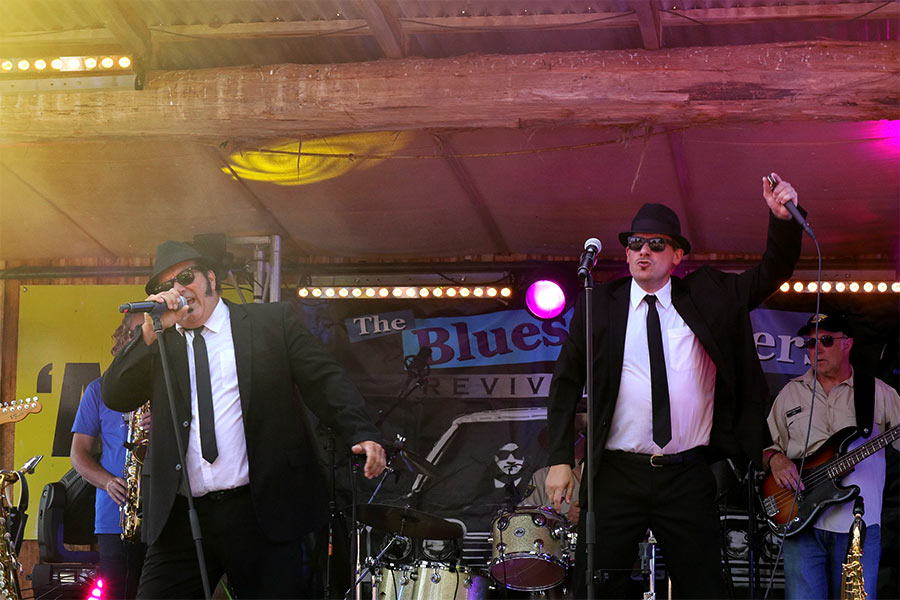 Two men in black tuxedos, hats and dark sunglasses hold microphones and are performing on stage. There's a band behind them.