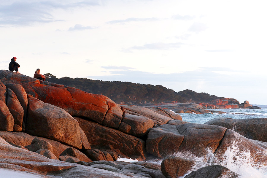 The sight of lichen covered boulders is broken by sea spray. Two people sit atop the rocks looking out to sea and a coastline of dense trees is in the background.
