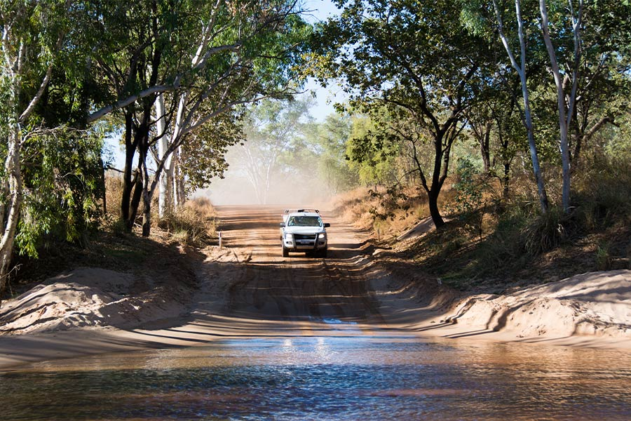 A white 4WD approaches a flooded overpass on a dusty outback road.