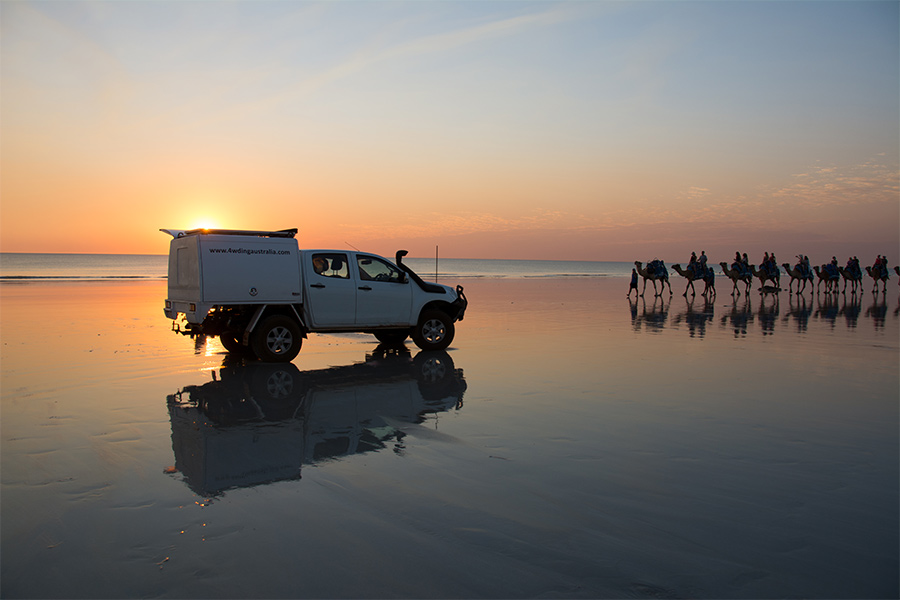An idyllic sunset over Cable Beach with a 4WD reflected onto the damp sand and camels silhouetted in the background.