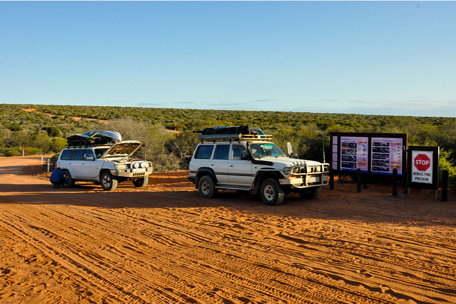 Two 4WD vehicles parked to the side of an outback track. Blue skies and saltbush make up the background and there are a couple of signs on the roadside.