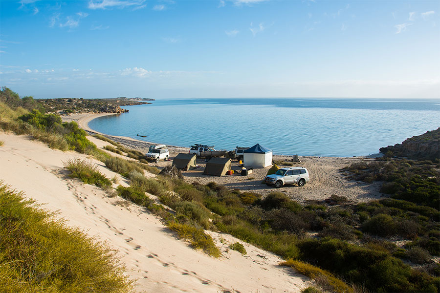 A wide shot of a remote beach camp where the dunes meet the sea. There's a group of tents and 4WDs on the sand.