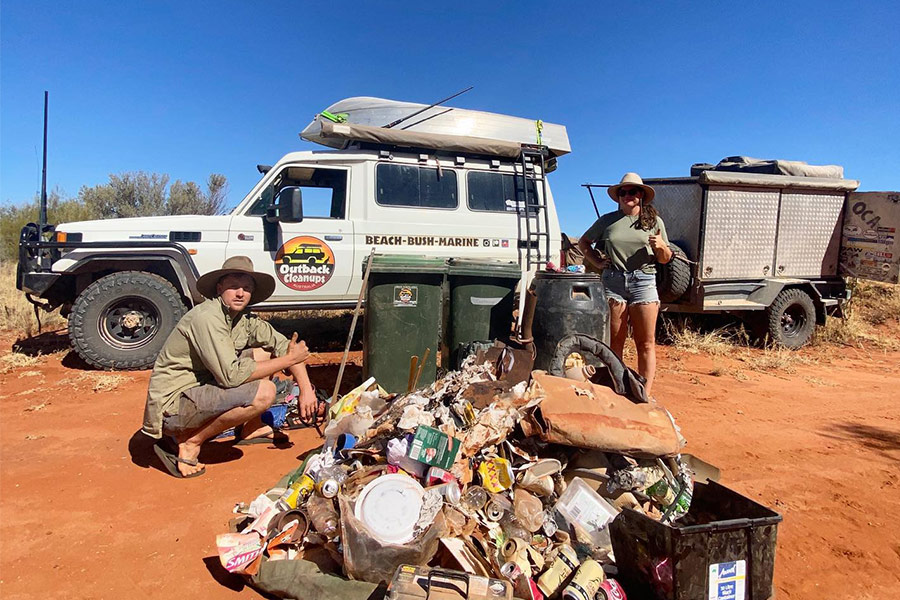 A massive pile of rubbish sits in the foreground with Outback Cleanups 4WD and trailer behind. Boe from the NGO squats down beside the rubbish on the left with his thumb up and Kimberley stands behind on the right with her thumb up. They're in the outback with red dirt around them.