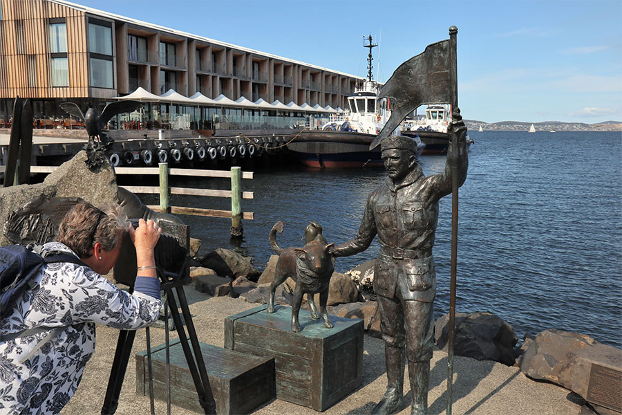 Kings Pier Marina Hobart - a woman is leaning over and pretending to look through an old tripod camera at the Bernacci Tribute sculpture.