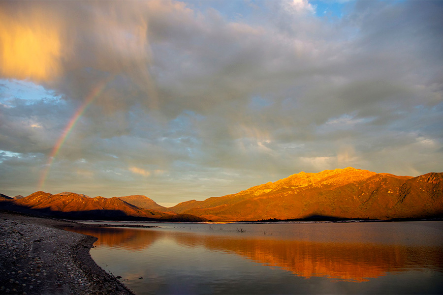 A sunset across Lake Burbury with the surrounding mountains creating a glowing backdrop. A mix of white and grey clouds are scattering the sky along with part of a rainbow to the left of frame.