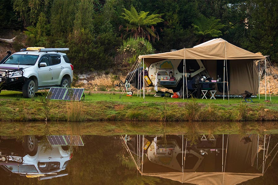 A lakeside camp setup with the lake in the foreground and camper pitched on the grass behind. There's a white 4wd off to the left of frame with portable solar panels in front.
