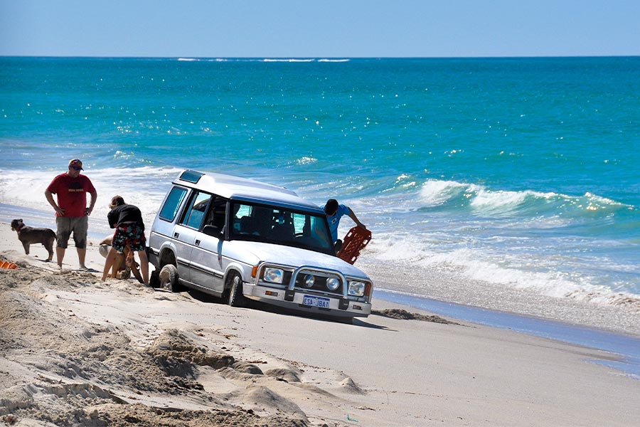 A white 4WD is bogged in the sand on a beach by the shoreline of blue ocean. There are a few people around the back wheels trying to get the car out. One man on the right holds a recovery track.
