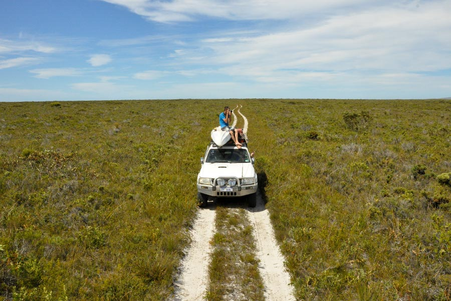 A wide open grassy plain with a sandy track running through the middle. There's a 4WD stopped on the track with a kayak strapped on top and a man sitting on the roof taking a photo.