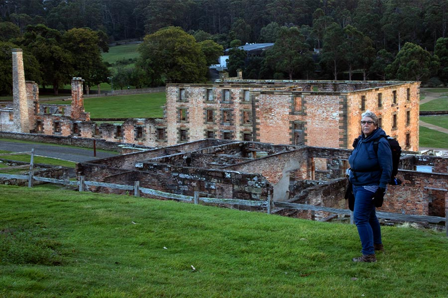 The Port Arthur historic site at dawn. A woman poses for the camera on the green grass in the foreground with the brick ruins behind.