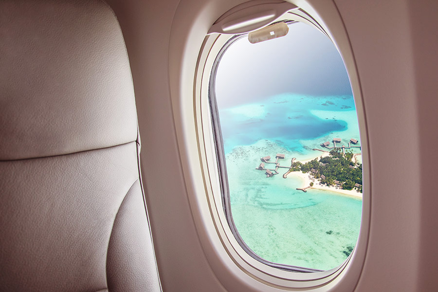 An aerial tropical view out an airplane window. There's a small island surrounded by turquoise water.