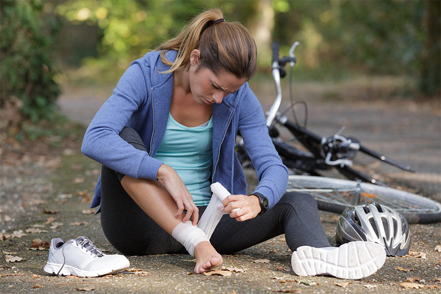 A female cyclist is sitting in front of her bike on a trail. She is strapping her ankle with a compression bandage.
